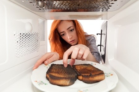 Girl look to a burned toasts in microwave photo