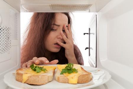 Atrakcyjna dziewczyna wyglÄ…da w kuchence mikrofalowej