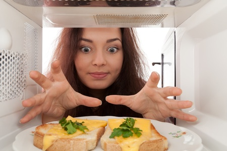 Attractive girl looks in a microwave Stock Photo
