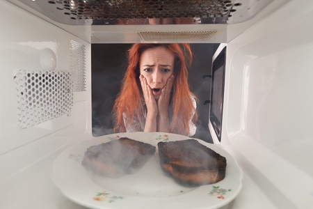 Young girl burn toasts in a microwave photo