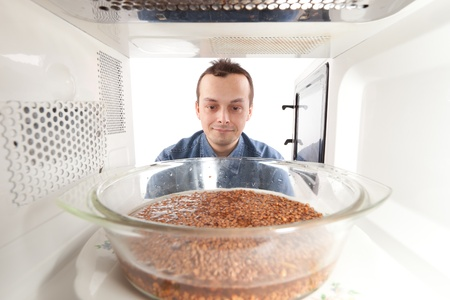 A man prepares buckwheat in the microwave