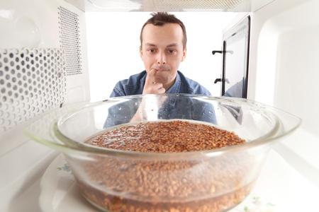 A man prepares buckwheat in the microwave photo