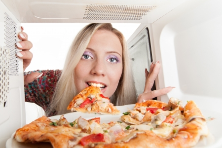Girl preparing pizza in the microwave photo