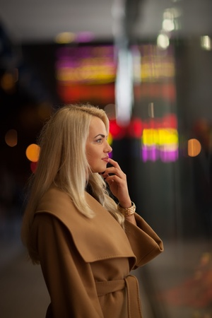 Beautiful girl looking in the shopwindow on the night city street photo