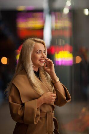 shopwindow: Beautiful girl looking in the shopwindow on the night city street Stock Photo