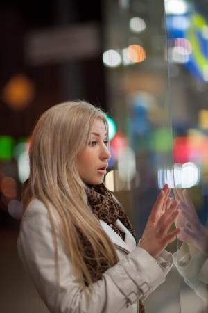 Belle fille dans la vitrine sur la rue de ville de nuit