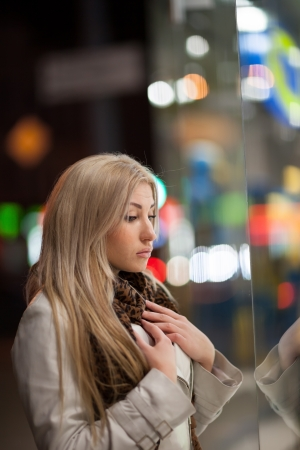 Beautiful girl looking in the shopwindow on the night city street Banque d'images