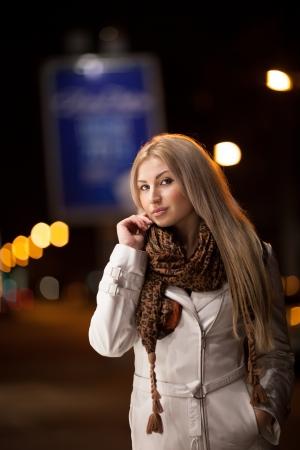 Belle fille marche dans une rue de ville de nuit