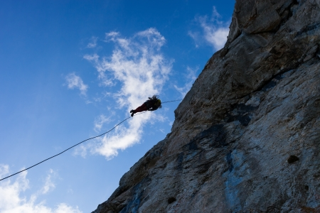 Silhouette of a rappelling man photo