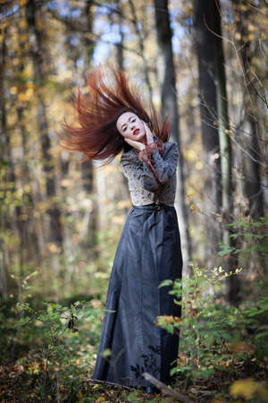 Young slim red autumn girl dance in autumn forest photo