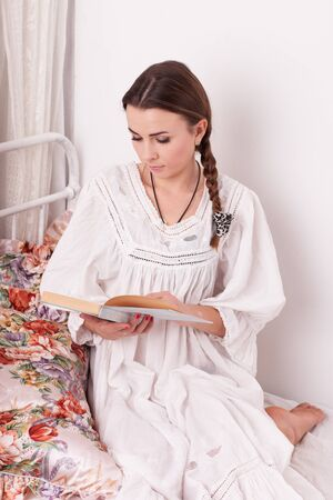 Young woman sit in a bed and read book Stock Photo - 16636763
