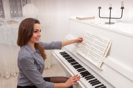 keyboard player: Young attractive girl play piano