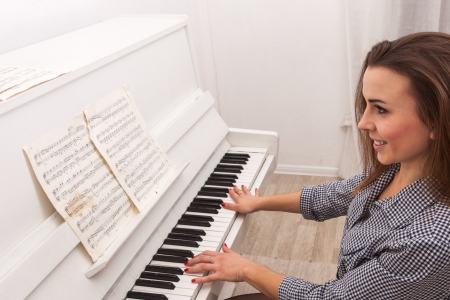 Young attractive girl play piano