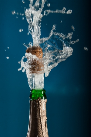 Opening a bottle of champagne with splashes photo