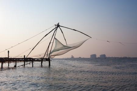 medias de red: Fishnets chinos en puesta del sol Kochi, Kerala, India Foto de archivo