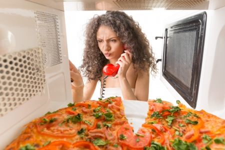 Girl preparing a pizza and talking on the phone photo