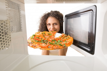 The girl gets a pizza out of the microwave photo