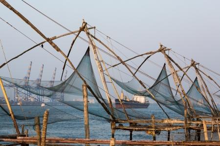 medias de red: Fishnets chinos en puesta del sol. Kochi, Kerala, India Editorial