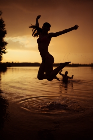Slender young girl jump in river at sunset photo