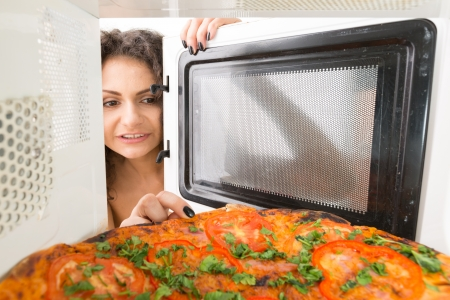frizz: Attractive girl open  a microwave