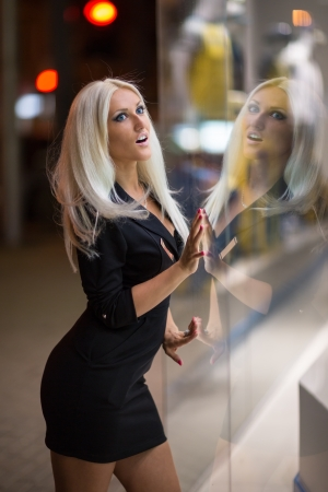 Beautiful blue-eyed girl looking in the shopwindow on the night city street photo