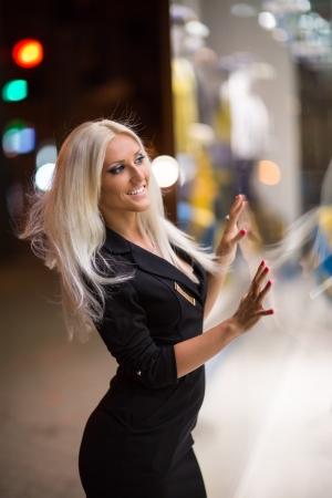 shopwindow: Beautiful blue-eyed girl looking in the shopwindow on the night city street
