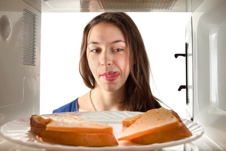 Girl lick to the sandwich. Through microwave oven view photo