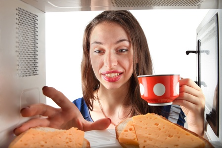 Girl stretch to the sandwich. Through microwave oven view photo