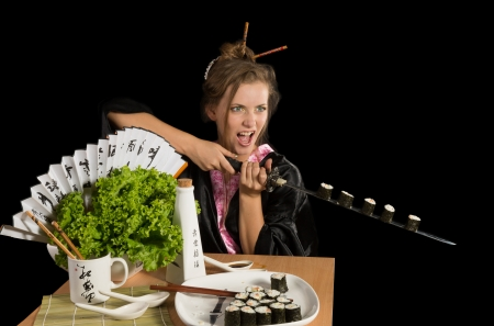 The young green-eyed beauty is holding sushi on katana photo