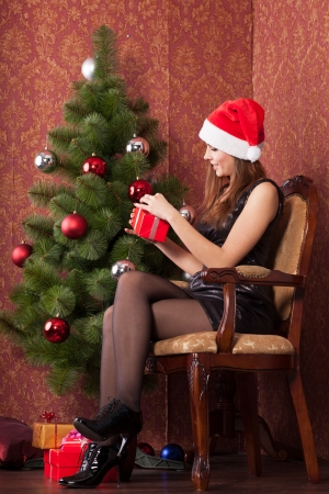 Attractive girl in a christmas hat opens a christmas gift photo
