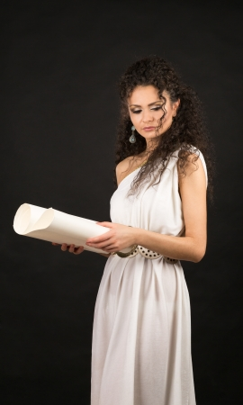 Ancient godness in a white greece toga on a black background holding a scroll Stock Photo