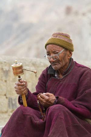 hindues: Anciano indio con la rueda de la oración en el umbral del templo