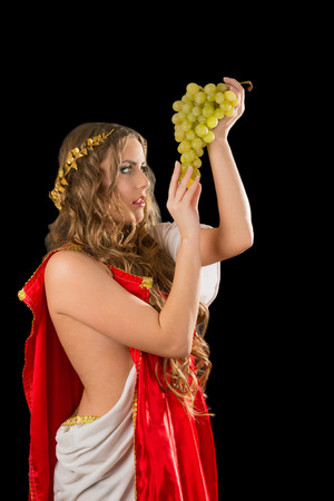 Ancient godness with a bunch of grapes isolated on a black background photo