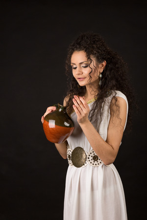 Curly girl in a Greek toga hold a jug photo