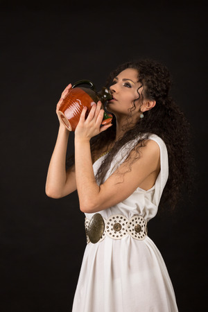 Curly girl in a Greek toga drink from a jug photo