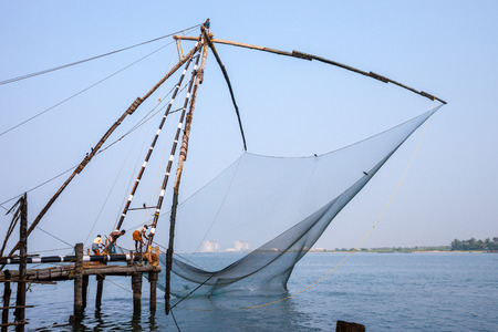 KOCHIN, INDIA-FEBRUARY 24: Fishermen on the city port on February 24, 2013 in Kochin, India. Indian fishermen using traditional Chinese network for fishing