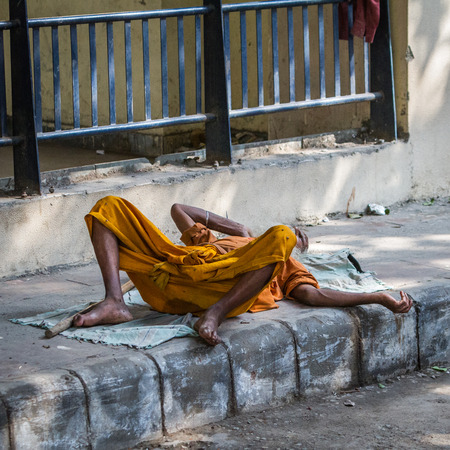 DELHI, INDIA-AUGUST 29: Hindu sleeping on the street on August 29, 2013 in Delhi, India. Hindu man sleeping on the city street