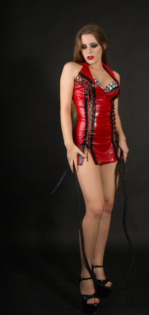 Sexy girl with a whip in red leather dress Stock Photo