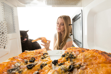 Girl and black cat looking at a pizza in the microwave