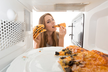 Girl looking at a pizza in the microwave