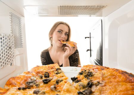 adult sandwich: Girl looking at a pizza in the microwave
