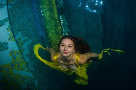 sea nymph: Graceful girl swimming underwater in a swimming pool. Stock Photo