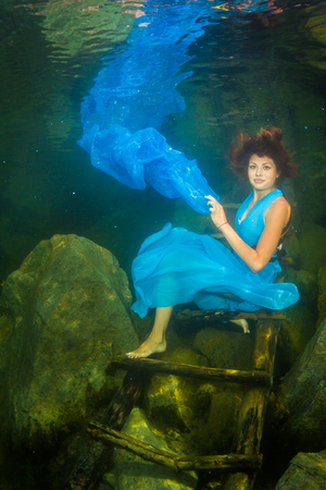 floats: Young graceful woman in a dress posing near the stairs in the lake