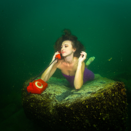 lies: The girl lies on the bottom of the lake and chatting on the phone Stock Photo