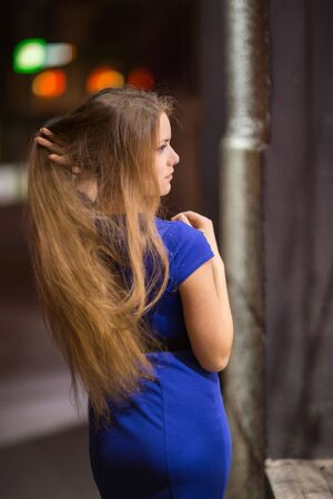 scrutinize: Cute green-eyed girl walking through the streets of the city at night Stock Photo