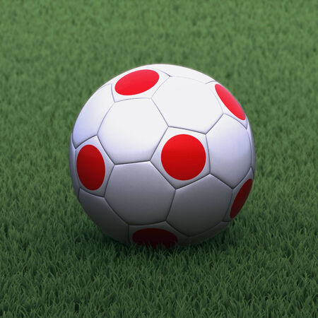 branded: football branded with the Japan flag on green grass Stock Photo