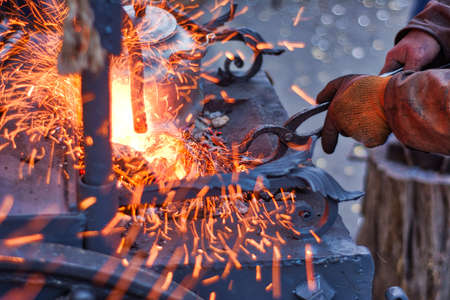 The smith is working on the horseshoe on a small forge furnace. Visible sparks in the forge and flying fire. Horseshoe forging at the Russian fair in Moscow. Standard-Bild