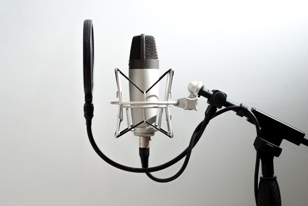 Microphone stand on wall background. Voice recording. On the air.
