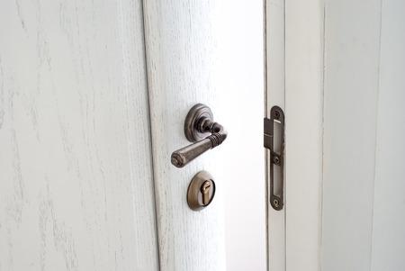 doorhandle: Open white wooden door. Entrance to the room