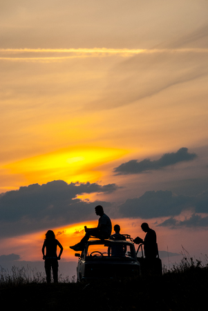 People and an old car on a sunset background. The man is resting on the roof of the car. Woman enjoying the sunset. Stok Fotoğraf